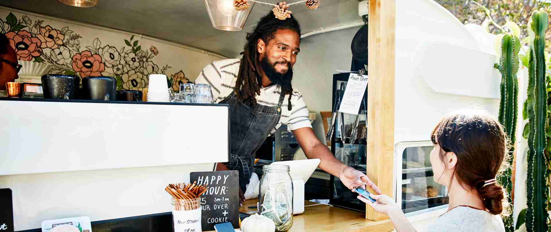 smiling african american man working in a food truck hands young woman a credit card