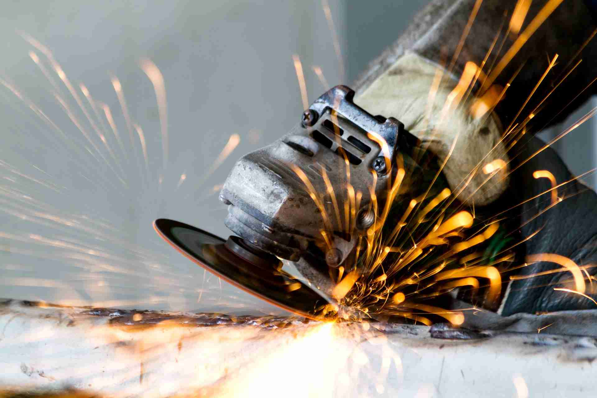 zoomed in view of a power tool welding with sparks flying