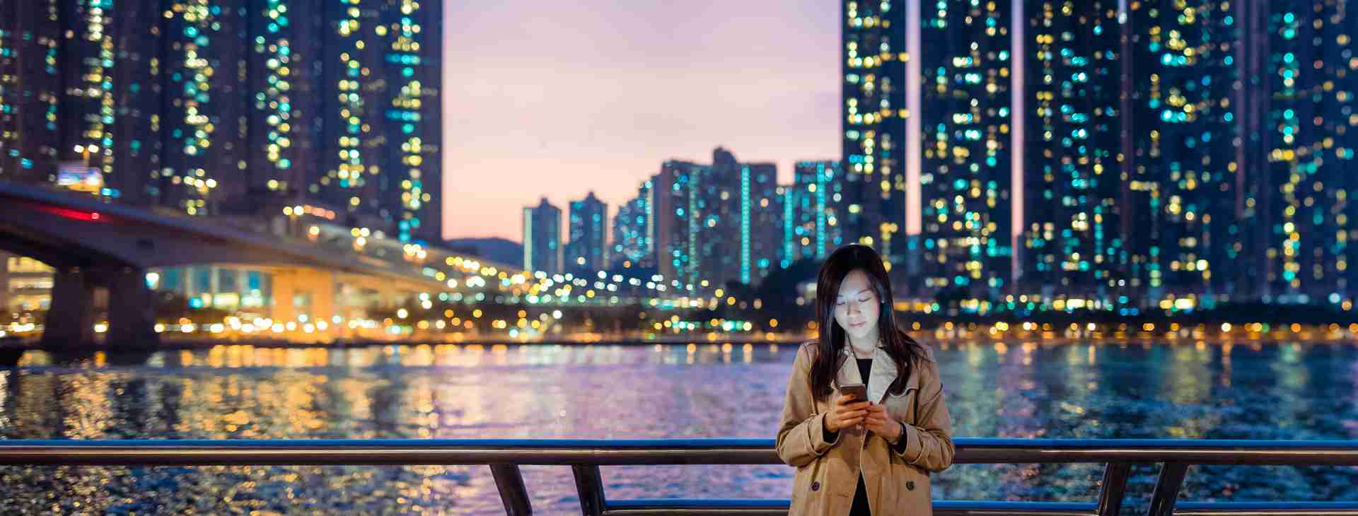 young asian woman on bridge at night looking at phone with skyscrapers behind her